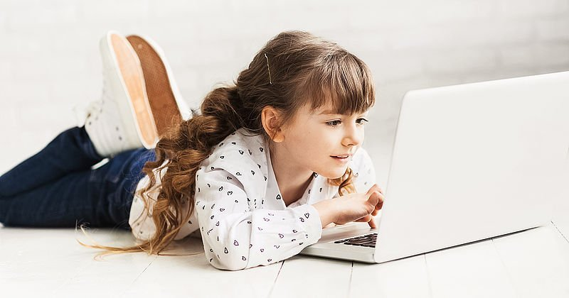 Cute little girl using laptop