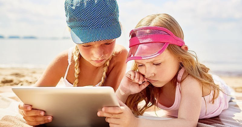 Kinder mit Tablet am Strand